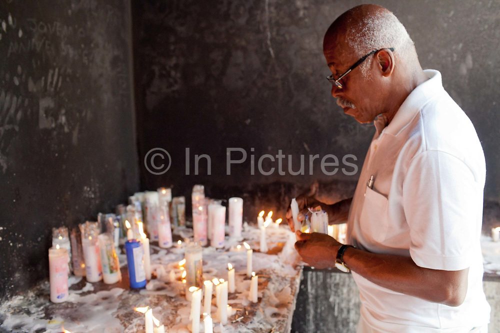 Man paying his respects to the dead with candles. Often the lines between Candomble and Catholicism are blurred. This is especially true with the Sao Lazaro event in late January in Salvador, Bahia, Brazil, the city which is known as the home of Candomble. Sao Lazaro represents healing and the sick.