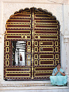 A woman sits on the doorstep of a grand building in Pushkar, Rajasthan, as another woman walks through the interior courtyard.