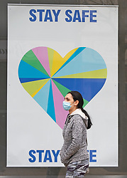 © Licensed to London News Pictures 17/03/2021. Bexleyheath, UK. A woman walking past a stay safe poster. People out and about shopping in Bexleyheath, South East London today are wearing masks to protect themselves during a third national coronavirus lockdown. Everyone over the age of fifty is now eligible for a Covid vaccine in the UK. Photo credit:Grant Falvey/LNP
