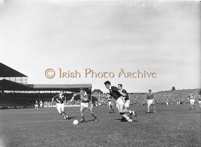 Kerry's D. Geaney crashes through the Galway defence pursued by Galway's S Colleran and F Erens during the All Ireland Senior Gaelic Football Championship Final, Kerry vs Galway in Croke Park on the 27th September 1959. Kerry 3-7 Galway 1-4. Alied Irish Bank Ansley Bridge Poplar Rd, Fairview North Srand, East Wall Rd Houses, Shiriff St Church Clouds Howth Cornmarket, St Brendans March 1987