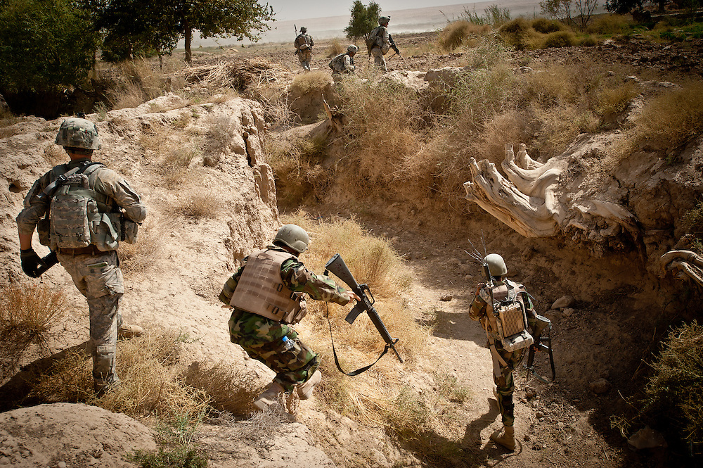 Soldiers jump down into a dry canal bed after a firefight, in pursuit of Afghan insurgents, who use the canal beds to maneuver without being seen.