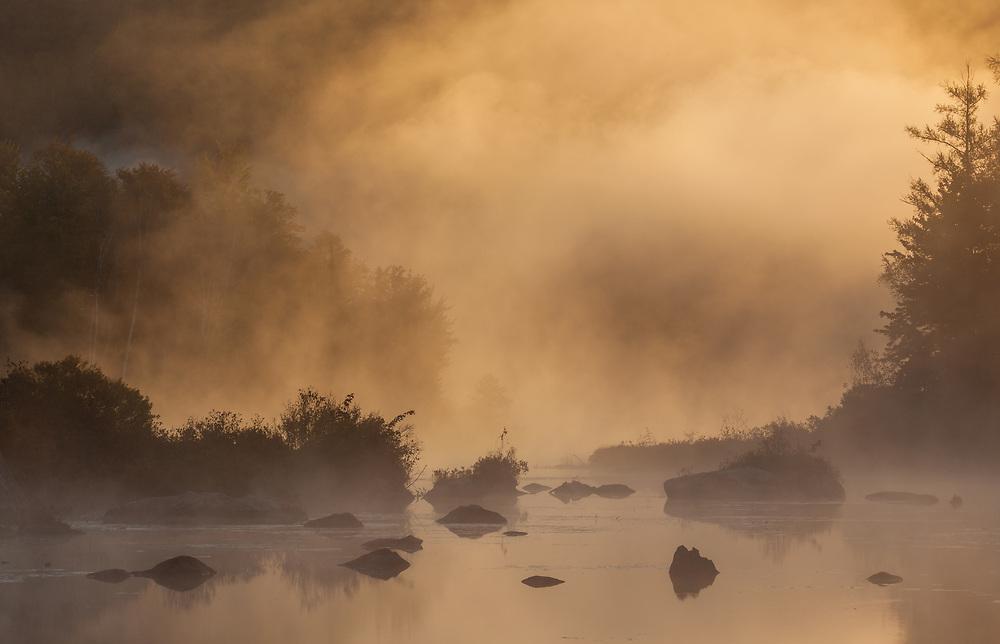 Warm light breaks through the early morning fog on Marshfield Pond, Marshfield, Vermont