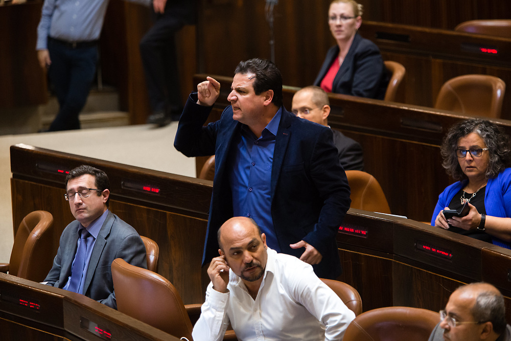 Arab-Israeli lawmaker, Member of the Knesset Ayman Odeh (C), confronts Israel's Minister of Internal Security Gilad Erdan (not pictured) at the Knesset, Israel's parliament in Jerusalem, on January 25, 2017.
