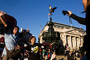 "An Asian couple pose for holiday photographs in London's Piccadilly Circus. While their friend holds a compact digital camera out to see the screen, the young people hold their arms out wide, almost echoing the spread wings of Eros, (""Intimate Love"" in Greek mythology), was the primordial god of sexual love and beauty. The statue known as Eros in Piccadilly Circus London, was made in 1893 and is one of the first statues to be cast in aluminium. The Circus is particularly known for its video display and neon signs mounted on the corner building on the northern side, as well as the Shaftesbury memorial fountain and statue of an archer popularly known as Eros (sometimes called The Angel of Christian Charity, but intended to be Anteros)."