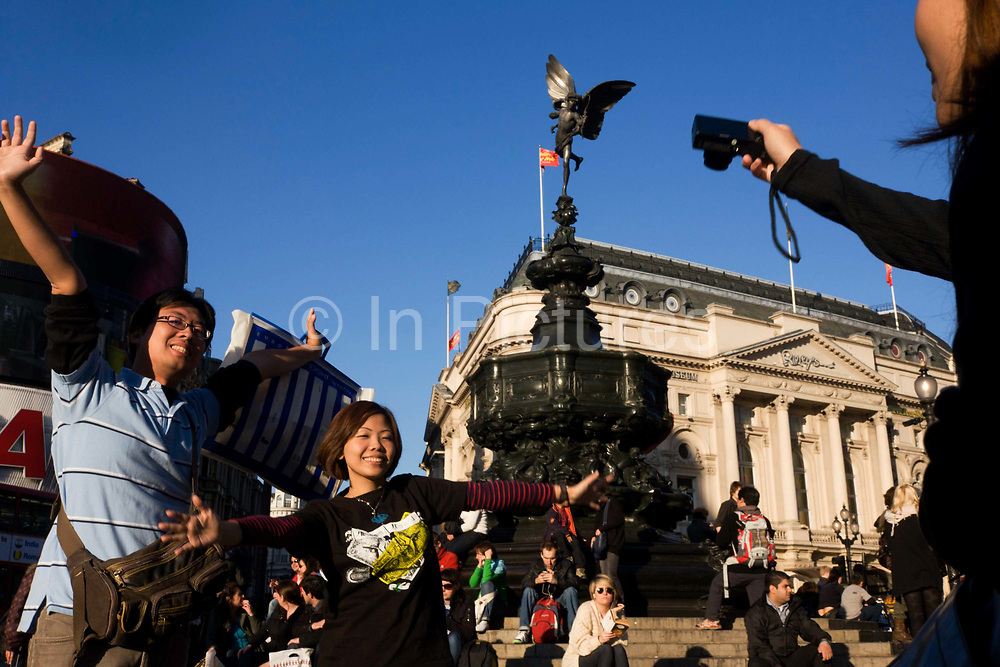 """An Asian couple pose for holiday photographs in London's Piccadilly Circus. While their friend holds a compact digital camera out to see the screen, the young people hold their arms out wide, almost echoing the spread wings of Eros, (""""Intimate Love"""" in Greek mythology), was the primordial god of sexual love and beauty. The statue known as Eros in Piccadilly Circus London, was made in 1893 and is one of the first statues to be cast in aluminium. The Circus is particularly known for its video display and neon signs mounted on the corner building on the northern side, as well as the Shaftesbury memorial fountain and statue of an archer popularly known as Eros (sometimes called The Angel of Christian Charity, but intended to be Anteros)."""