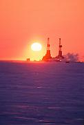 Alaska. North Slope. Prudhoe Bay. The sunset backlights oil derricks.