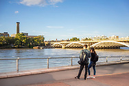 Two young adults looking across the river Thames in London from the south bank