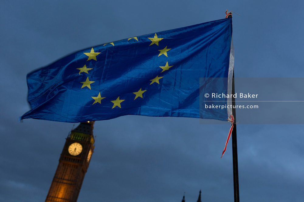 """An EU flag is waved in front of the British parliament as the British government debated US President Donald Trump's state visit to the UK, thousands of protesters gathered in large numbers against the trip which would potentially cost millions of Pounds in security alone. The visit comes after two online petitions received more than the 100,000 signatures required for such a debate to be considered in Parliament. A petition against the state visit got 1.85m signatures, while one supporting it got 311,000. Campaigners protested against the """"hatred, racism and division that Donald Trump is trying to create"""". Prime Minister Theresa May announced the state visit during her visit to Washington in January."""