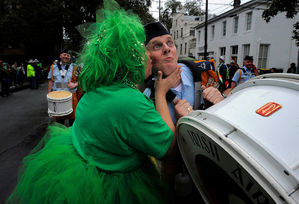 Carolyn Geis, right, kisses Irish Air Corps Pipe and Drum member Terry Healy on the cheek during Savannah's 190-year-old St. Patrick's Day parade, Monday, March 17,  2014, in Savannah, Ga. Kissing men in uniform is a tradition during the celebration in Georgia's first city.  (AP Photo/Stephen B. Morton)