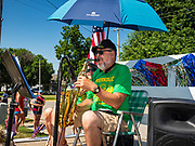 04 JULY 2020 - RUNNELLS, IOWA: A man plays the saxophone during the 4th of July tractor parade in Runnells, a small community about 25 miles from Des Moines. Most of the Independence Day parades in central Iowa were cancelled because of the COVID-19 (Coronavirus) pandemic. People in Runnells made the decision to go ahead with their parade, the first 4th of July parade in the town in recent memory. Most of the people in the parade were farmers, who drove their tractors through the town.     PHOTO BY JACK KURTZ