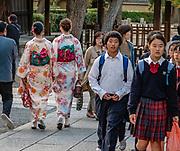 Kimono clad women and school uniformed kids in Gion district, Kyoto, Japan.