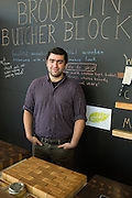 A representative from Brooklyn Butcher Block, which makes exquisite cutting boards from hardwoods, at the BklynDesigns show, part of NYCxDesign, a week-long design festival in New York City. On the table in front of him is a butcher block glue dup to look like brickwork.