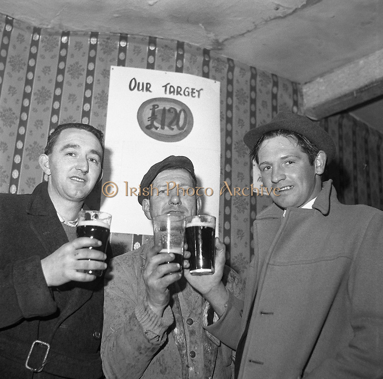 Limerick Widows Alms House. Pint drinkers, from left, David Quinn, Christopher 'Buster' MacNamara and Tony Doherty, pay a penny extra on a pint towards the widows electric light..28.03.1962
