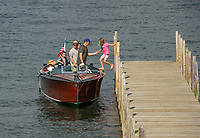 A young girl is helped on board a boat at the Weirs Beach docks.  Karen Bobotas for the Laconia Daily Sun