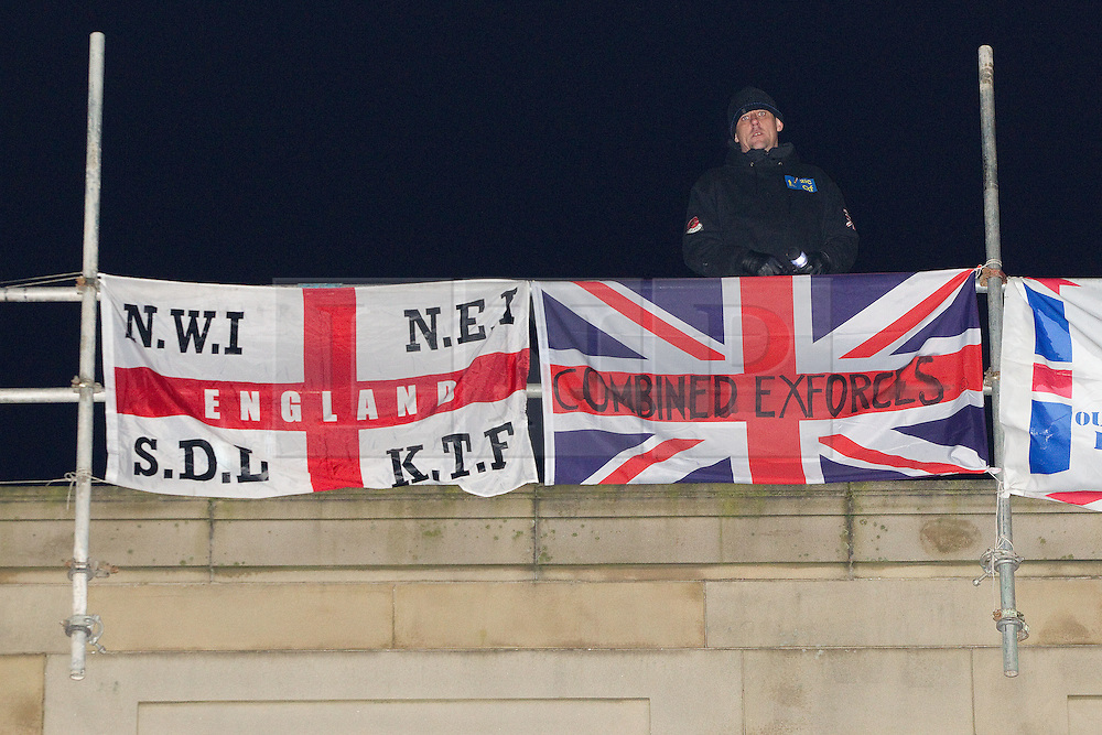 """© licensed to London News Pictures. Bury, UK  03/03/2012. Following a National Front demonstration in nearby Heywood, groups known as the """"North West Infidels"""" and the """"Combined Ex Forces"""", splinters of the EDL and other far-right organisations, are staging a rooftop protest on Bury Town Hall. Police said the group had climbed up scaffolding at the side of the Town Hall to gain roof access. They have affixed banners stating """"Hang paedo scum"""" along with nationalist slogans. Photo credit should read Joel Goodman/LNP"""