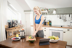 Young woman cutting slices of watermelon in the kitchen, Bavaria, Germany