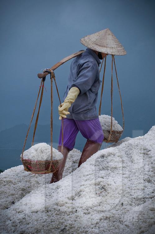 Vietnamese worker harvest brackish in salt marsh of Doc Let, Vietnam, Asia. Carries salt in baskets with help of its yoke. Labor in salines is done by women.