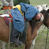 A young nomadic herder naps on his horse during a naadam festival on a remote pass near Muren, Mongolia.