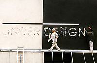 6/15/05-LOS ANGELES- Workers de-sign a design sign on an out-of-business furniture store on La Brea  Wednesday. David Sprague/Daily News