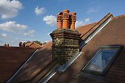 Rooftop view of a suburban Edwardian semi-detached house in south London. We are high up at roof level on a sunny afternoon in the borough of Lambeth where  middle-class houses were built around the time of the first world war and whose building workforce probably did not return. A Velux window has been fitted in the converted attic that many house owners invest in to increase space and value.
