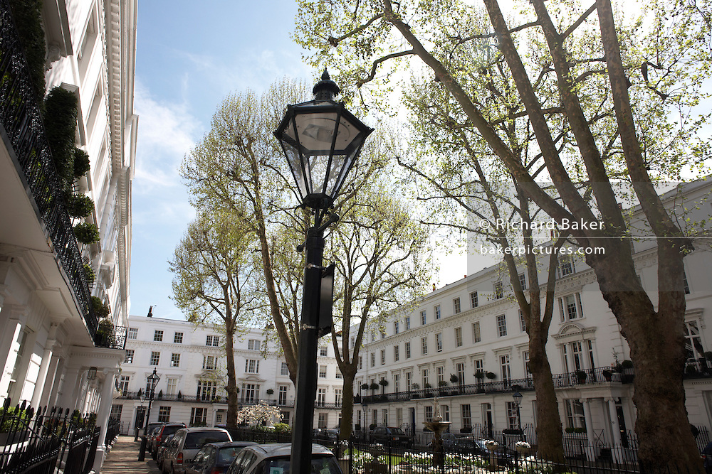 Immaculate and identical white-painted properties and ornamental lamp post in exclusive Wellington Square, SW1