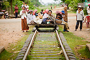 """01 JULY 2006 - PHNOM PENH, CAMBODIA: Passengers wait for a bamboo train to get underway in central Cambodia. The """"bamboo trains"""" run along the government tracks in rural Cambodia. Bamboo mats are fitted over wheels which ride on the rails. The contraption is powered by a either a motorcycle or lawn mower engine. The Cambodian government would like to get rid of the bamboo trains, but with only passenger train in the country, that runs only one day a week, the bamboo trains meet a need the government trains do not. While much of Cambodia's infrastructure has been rebuilt since the wars which tore the country apart in the late 1980s, the train system is still in disrepair. There is now only one passenger train in the country. It runs from Phnom Penh to the provincial capitol Battambang and it runs only one day a week. It takes 12 hours to complete the 190 mile journey.  Photo by Jack Kurtz / ZUMA Press"""