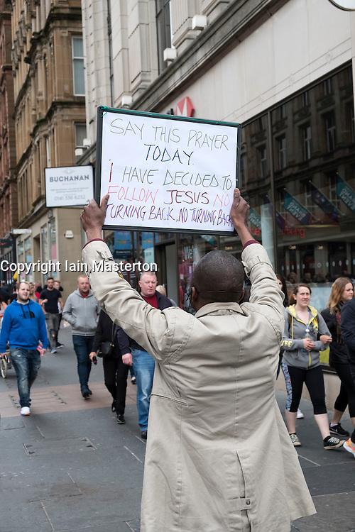 Man holding sign promoting Christianity on Buchanan Street in Glasgow United Kingdom