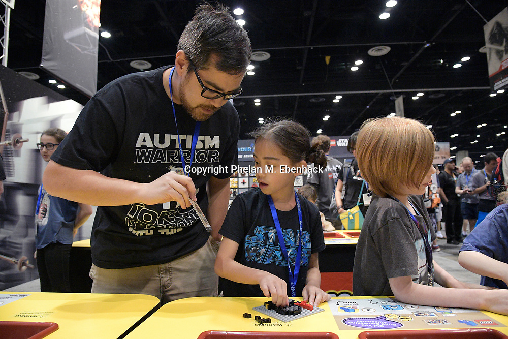 Mischa Salkin, 7, of Miami, builds a movie-themed Lego model from a photo shown by her father, Jon Salkin, during the Star Wars Celebration event in Orlando, Fla., Friday, April 14, 2017. (Photo by Phelan M. Ebenhack)