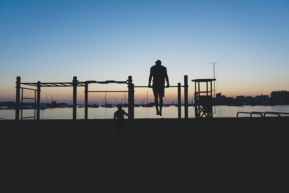 Sant Antoni de Portmany, Ibiza, Spain - July 29, 2018: Two men workout at sunset at the beach in Sant Antoni (San Antonio), Ibiza.