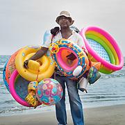 Alberto Montalvan vende flotadores hace 29 años. Los precios varian entre 7.000 pesos y 15.000 pesos. Lleva consigo 25 flotadores y vende 30 o 35 en alta temporada. Llega a la playa a las 6am y le toma dos horas inflar los flotadores. Empieza la venta a las 8am hasta las 5pm. Trabaja los 365 dias al año. Es su propio dueño.  Si se pone protector solar cuando su esposa saca las muestras de las revistas.