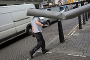A deliveryman carries the rear of a long roll of carpet into a nearby building off Leicester Square, on 5th March 2018, in London, England.