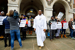 © Licensed to London News Pictures. 15/02/2017. London, UK. Choir singers walk past LGBT campaigners, including Peter Tatchall, holding a protest vigil outside the General Synod of the Church of England, where same sex marriage is due to be debated. Photo credit: Tolga Akmen/LNP