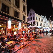 A cobblestone street in downtown Brussels at night.