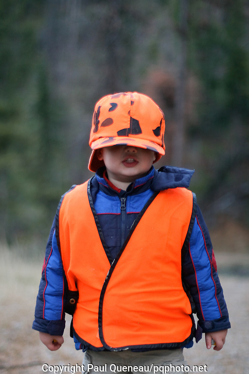 Jackson Queneau, 3, deals with the perils of oversized hunting wardrobe.