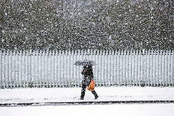 © Licensed to London News Pictures. 29/04/2016. Leeds UK. Picture shows a woman walking to work in the snow this morning. Leeds woke to a covering of snow this morning & is expected to get further snow showers over the weekend. Photo credit: Andrew McCaren/LNP