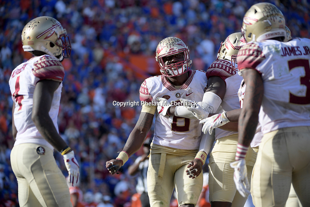 Florida State linebacker Matthew Thomas (6) holds a piece of the turf that he pulled up after intercepting a pass during the second half of an NCAA college football game against Florida Saturday, Nov. 25, 2017, in Gainesville, Fla. FSU won 38-22. (Photo by Phelan M. Ebenhack)