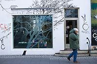 A man walks by a shoestore in Laugavegur, 101 Reykjavík, smoking his cigarette. Maður gengur fram hjá skóbúð á Laugavegi og fær sér smók.