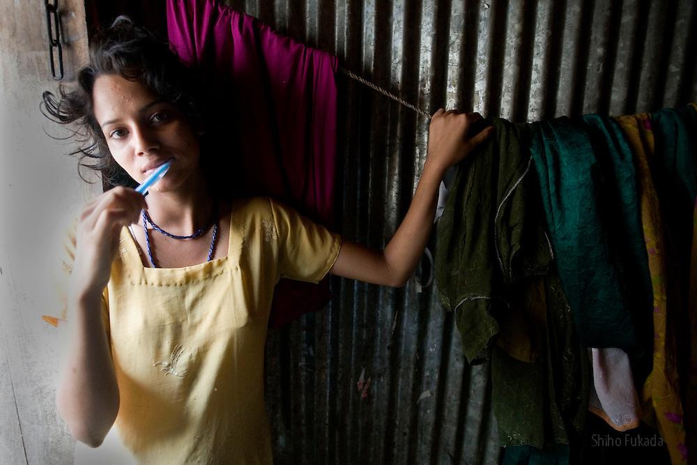 Sex worker Shetu, 17, brushes her teeth at brothel in Tangail, Bangladesh.