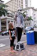 """8 year old child standing beside """"living statue"""" busker in Waikiki, Honolulu, Hawaii RIGHTS MANAGED LICENSE AVAILABLE FROM www.PhotoLibrary.com"""