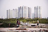 A motorbike goes off track in a suburb area of Hanoi, Vietnam, Asia. Ciputra's towers raise in background.