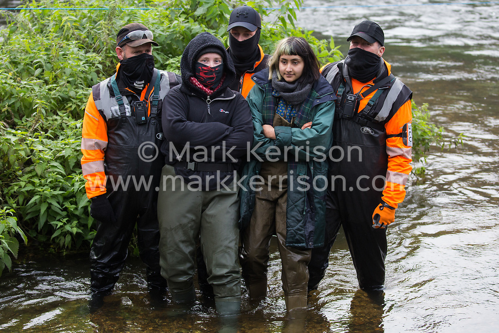 HS2 security guards stand behind female anti-HS2 activists in the river Colne at Denham Ford during bridge building works for the HS2 high-speed rail link on the first day of the second national coronavirus lockdown on 5 November 2020 in Denham, United Kingdom. Prime Minister Boris Johnson has advised that construction work may continue during the second lockdown but those working on construction projects are required to adhere to Site Operating Procedures including social distancing guidelines to help prevent the spread of COVID-19.