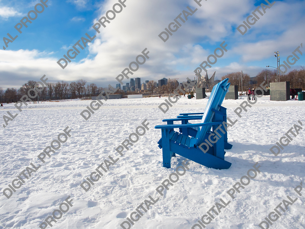 January 09, 2021 - Montreal, Canada Outdoors chairs in the snow at Park Jean-Drapeau in winter with Montreal buildings in the background