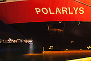 "View of the bow of the Hurtigruten ship ""Polarlys"" (Polar Lights), framing the Ishvaskatedralen or the Arctic Church, across the fjord in Tromsdalen, photographed at night."