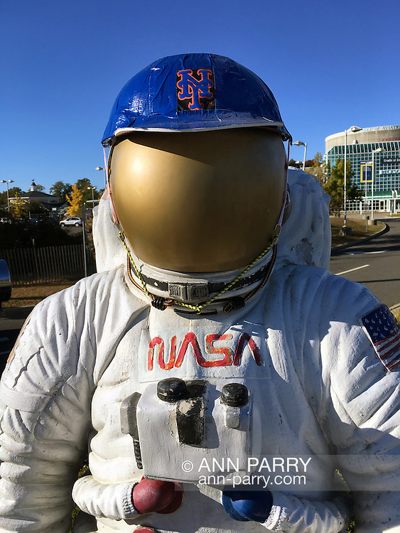 Garden City, New York, USA. October 23, 2015. When New York METS clinch a trip to the World Series, the NASA astronaut statue at entrance to Long Island Cradle of Aviation Museum looks like big METS fan, wearing blue and orange Mets cap. On October 19, the Mets completed their sweep against Chicago Cubs in the National League Championship Series.