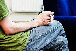 A man holding a mug during a coffee break.