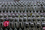 Some of the many Jizo statues, that are meant to comfort the souls of unborn children, surrounding Jizo Do hall at Hasedera Temple in Kamakura, Kanagawa, Japan. July 7th 2010