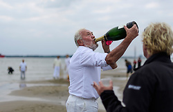 © Licensed to London News Pictures. 18/09/2016. Portsmouth, UK. A bowler takes a swig of champagne before bowling. Teams take part in the  Bramble Bank Cricket Match in the middle of The Solent strait on September 18, 2016. The annual cricket match between the Royal Southern Yacht Club and The Island Sailing Club, takes place on a sandbank which appears for 30 minutes at lowest tide. The game lasts until the tide returns. Photo credit: Ben Cawthra/LNP