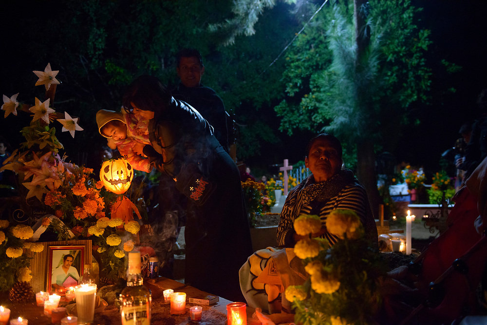 """During Day of the Dead celebrations (""""Día de los Muertos"""" in Spanish), a family sits beside a loved one's decorated grave at the cemetery in Xoxocotlán, on the outskirts of Oaxaca, Mexico. A tequila bottle, photograph, flowers, and candles are on the grave."""