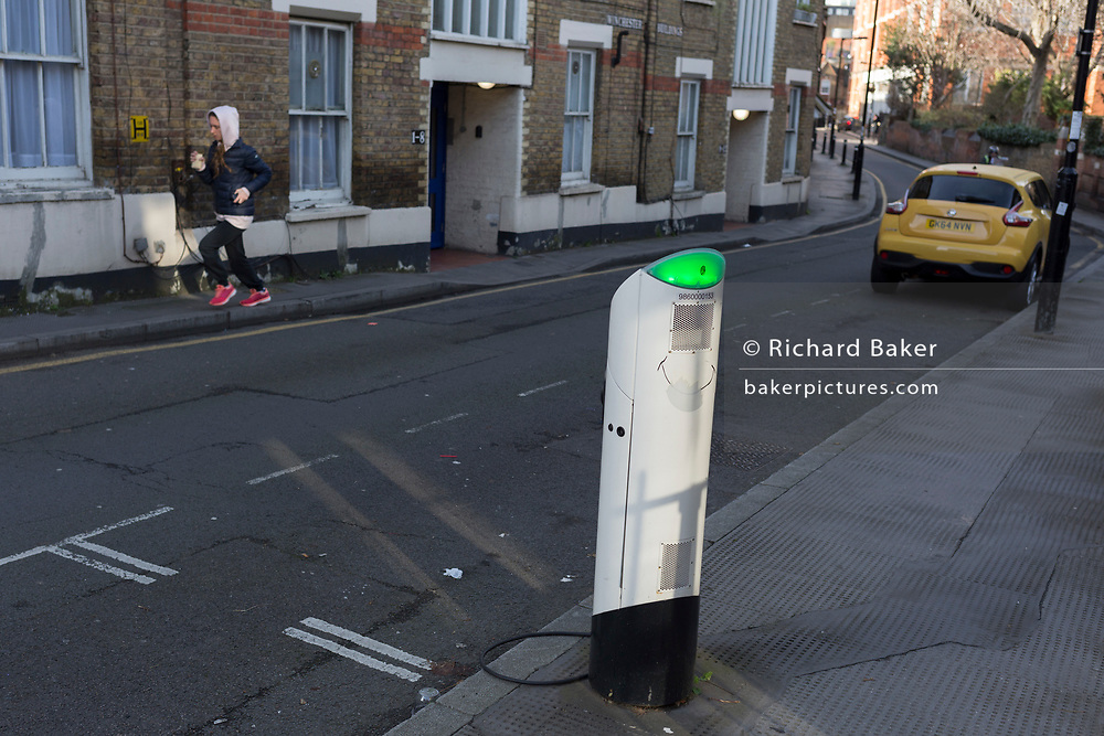 An electric car re-charging point and a jogger, on 30th January 2018, in the south London borough of Southwark, England.