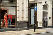 Man painting a doorway next to the Gucci store on Bond Street on 25th May 2021 in London, United Kingdom. These high end brands are seen next to each other on a very ordinary wall. Bond Street is one of the principal streets in the West End shopping district and is very upmarket. It has been a fashionable shopping street since the 18th century. The rich and wealthy shop here mostly for high end fashion and jewellery.